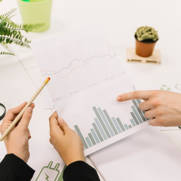 Group of businesspeople hand analyzing graph at workplace Free Photo