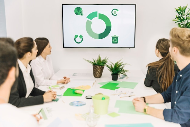 Group of businesspeople looking at natural resources icon in meeting Free Photo
