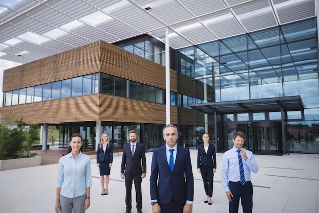 Gruppo di persone di affari che stanno l'edificio per uffici esterno Foto Gratuite