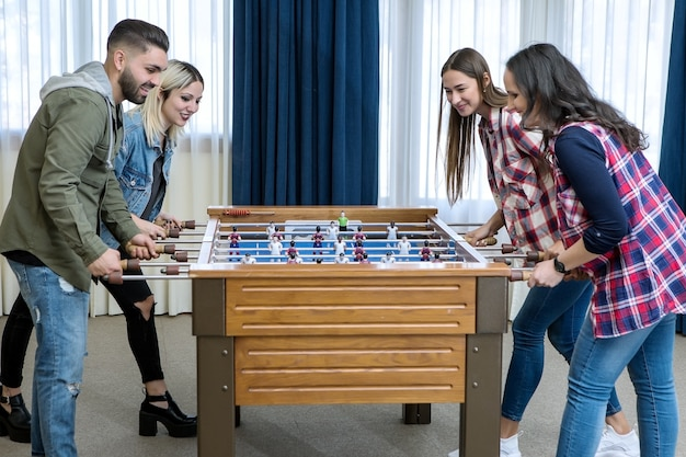 Group of cheerful friends playing table football Premium Photo