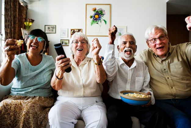 Group of cheerful senior friends sitting and watching tv together Premium Photo