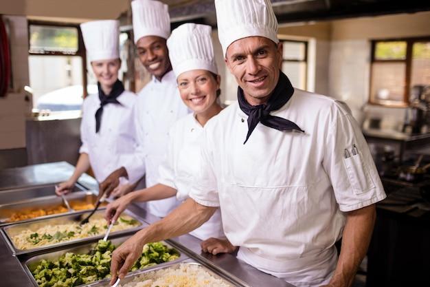 Group of chefs stirring prepard foods in kitchen Premium Photo