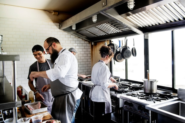 Group of chefs working in the kitchen Free Photo