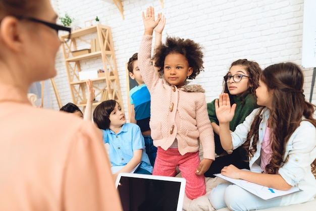 Group of children are pulling hands to answer teacher. Premium Photo