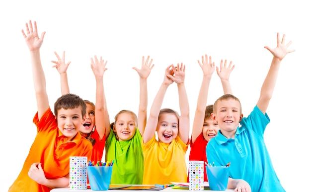 Gruppo di bambini in magliette colorate seduti a un tavolo con le mani alzate. Foto Gratuite