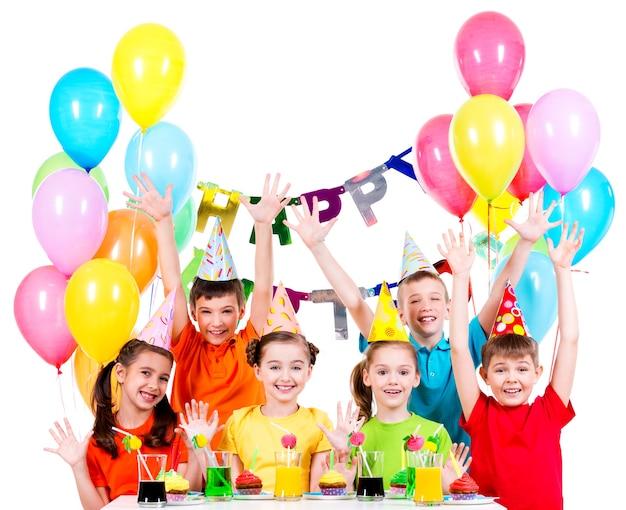 Gruppo di bambini in camicie colorate alla festa di compleanno con le mani alzate - isolato su un bianco. Foto Gratuite