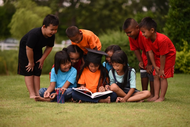 Group of children lying reading on grass field Free Photo
