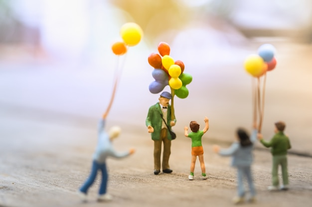 Group of children miniature people figure standing and walking around a man balloon seller Premium Photo