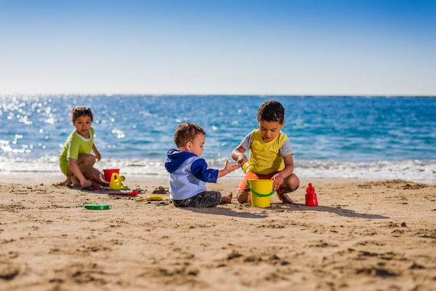 Group of children playing with beach toys under sunlight Premium Photo