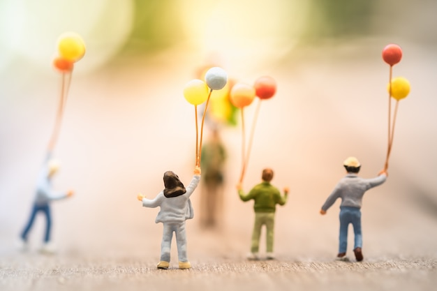 Group of children standing and walking abd running to a man balloon seller Premium Photo