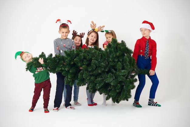 Un gruppo di bambini cerca di sollevare l'albero di natale Foto Gratuite