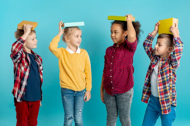 Group of childrens with books on head Free Photo