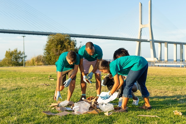 Group of cleaning workers collecting trash outdoors Free Photo