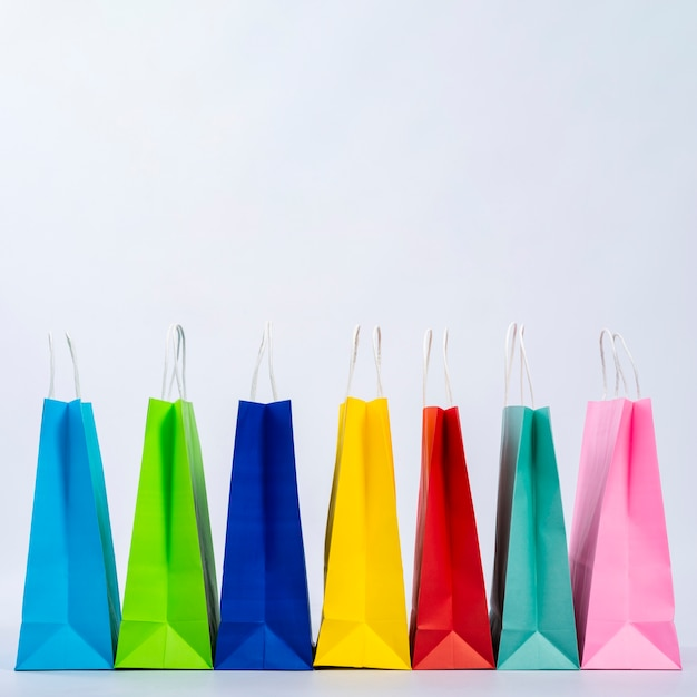 Group of colourful bags displayed in a row Free Photo