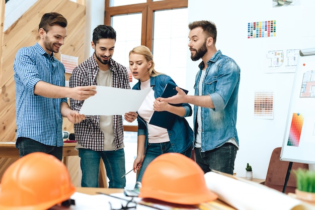 Group of designers architects look at blueprint. Premium Photo