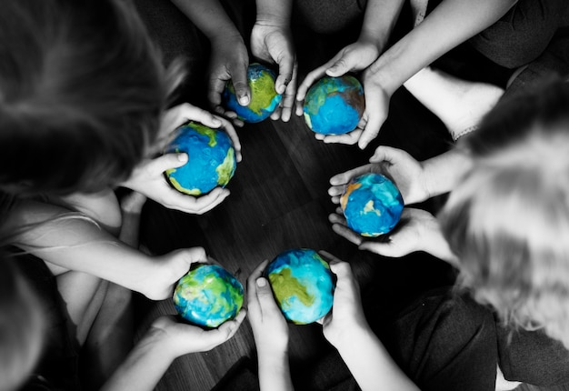 Group of diverse kids hands holding cupping globe balls together Free Photo