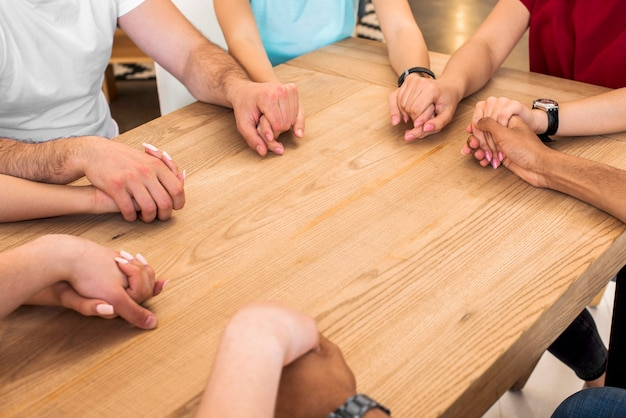 Group of diverse people holding hands on wooden desk Free Photo
