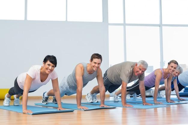 Группа делает отжимания в ряду в классе йоги Premium Фотографии