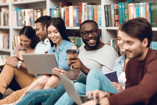 Group of ethnic multicultural smiling and talking in library Premium Photo