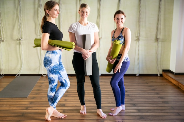 Group of female friends in sportswear smiling together while standing in a gym after yoga workout. Premium Photo