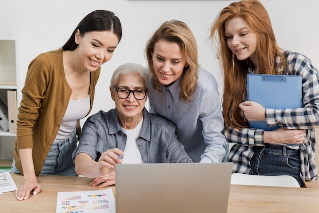 Group of females working together on a laptop Free Photo