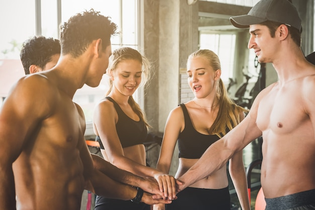 Group of fitness people men and woman put the hands together for team work. happy fitness workout team concept. Premium Photo