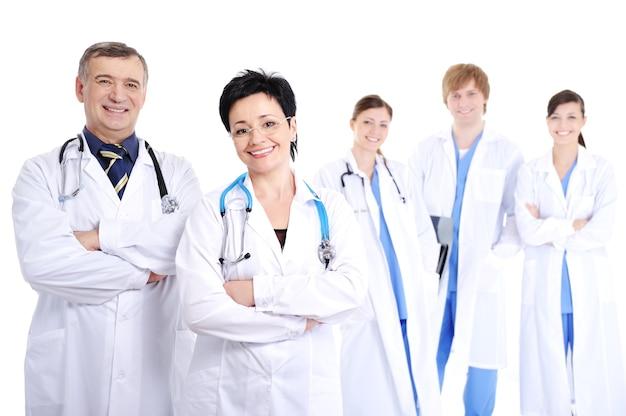 Un gruppo di cinque medici allegri sorridenti felici in camici dell'ospedale Foto Gratuite