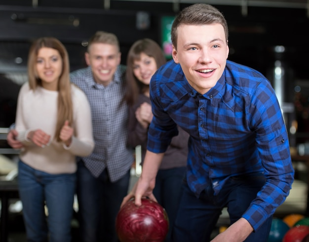 Group of four friends in a bowling alley having fun. Premium Photo