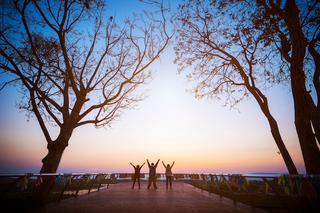 Group of four people stands on the top of mountain in winner pose. Premium Photo