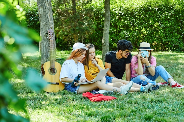 Un gruppo di quattro giovani che si divertono nel parco, seduti sull'erba Foto Gratuite