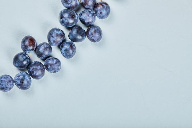 Gruppo di prugne fresche sull'azzurro. Foto Gratuite