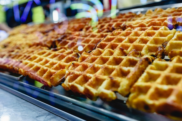 Group of freshly baked waffles ready to be savored for sale at a fair. Premium Photo