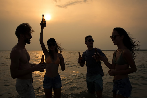 Group of friends celebrating and drinking at the beach in twilight sunset Premium Photo