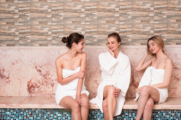 Group of friends chatting by the pool at spa Free Photo