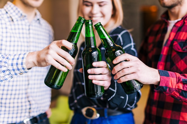 Group of friends clinking beer bottles in the pub Free Photo