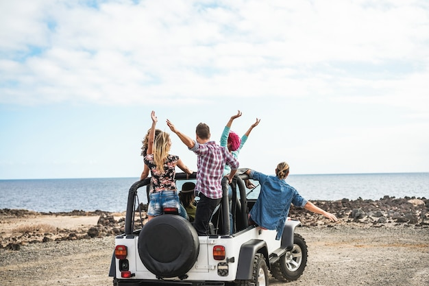 Group of friends doing excursion around desert with convertible 4x4 car - friendship, tour, youth, lifestyle and vacation concept - focus on guys bodies Premium Photo