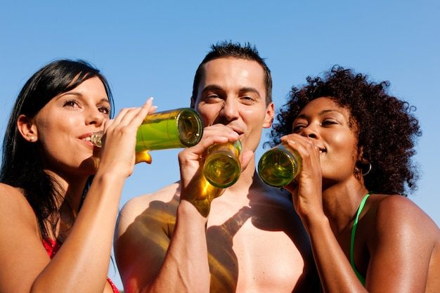 Group of friends drinking beer in swimwear Premium Photo