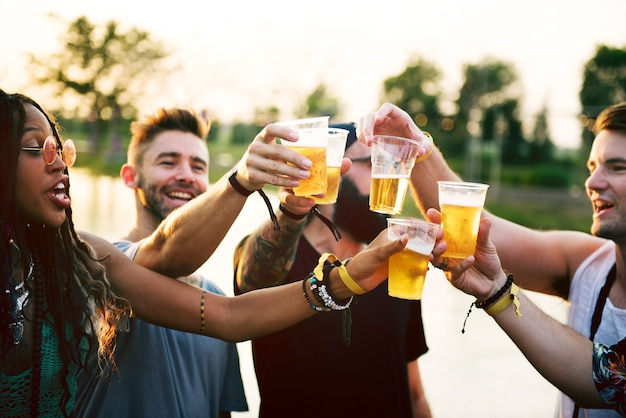 Group of friends drinking beers enjoying music festival together Premium Photo