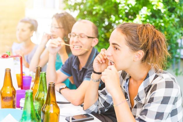 Group of friends eating meat skewers Premium Photo
