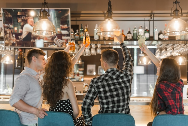 Group of friends enjoying drinks in bar Free Photo