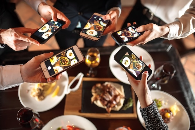 Group of friends going out and taking a photo of food together with mobile phone Premium Photo