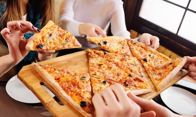 A group of friends grab a fresh hot pizza sitting in a cafe Premium Photo