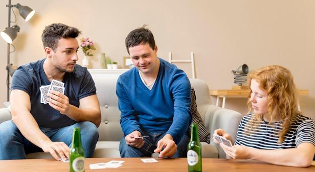 Gruppo di amici che mangiano birra e carte da gioco a casa Foto Gratuite