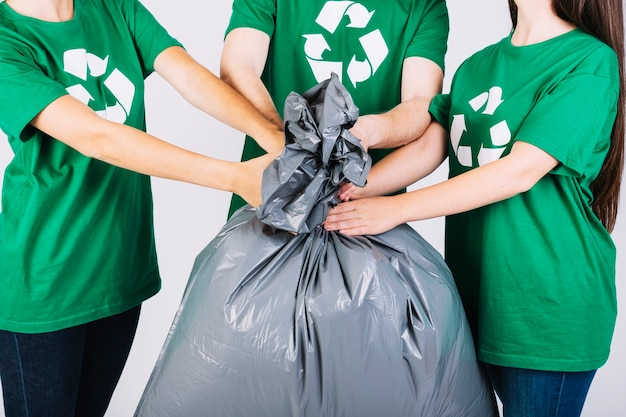 Group of friends holding garbage bag Free Photo