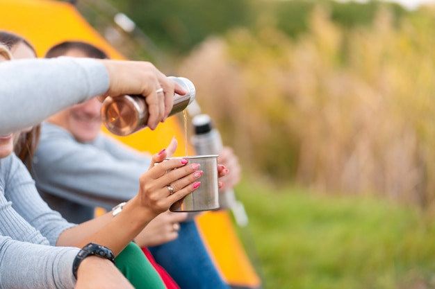 A group of friends is enjoying a warming drink from a thermos, on a cool evening by a fire in the forest Premium Photo