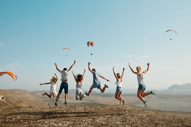 Group of friends jumping on top of hill Free Photo