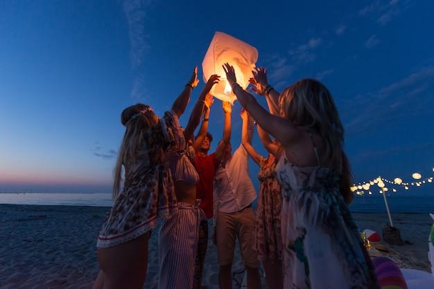 Group of friends lighting lanterns Premium Photo
