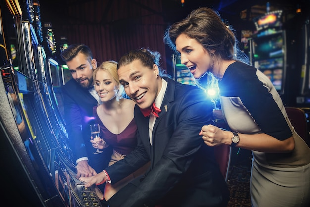 Group of friends playing slot machines Premium Photo