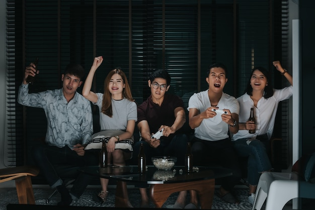 Group of friends playing video games on tv at home, noise and grain
