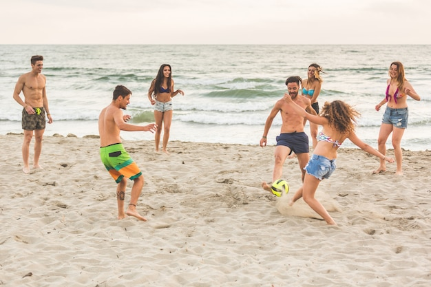 Group of friends playing with ball on the beach Premium Photo
